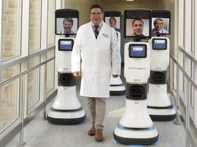Dr. Ivar Mendez walks alongside remote controlled robots used to allow doctors to interact with patients in far-flung locations.