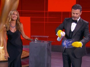 This handout screen shot shows host Jimmy Kimmel and actress Jennifer Aniston disinfecting ballots during the 72nd Primetime Emmy Awards held virtually on Sunday, Sept. 20, 2020.