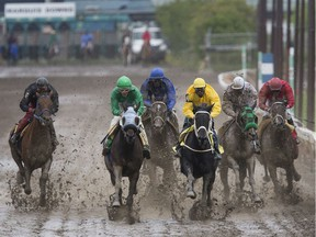 Naim Samara, in green, riding Miss Camelot battles for the lead with Garfield Gordon, in yellow, riding the horse Devirow during the second race at Marquis Downs  in Saskatoon on July 21, 2017.