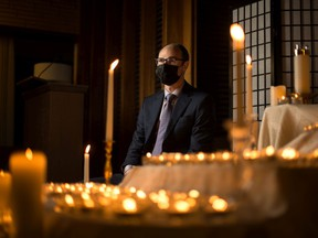 Funeral director Morgan Edwards is photographed with hundreds of candles at the Saskatoon Funeral Home, which symbolize the lives lost in Saskatchewan due to the COVID-19 pandemic. Photo taken in Saskatoon on Monday, March 15, 2021.