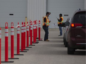 Health-care workers wait outside for patients at a drive-thru testing site for Covid-19 in Saskatoon, Saturday, September, 12, 2020.
