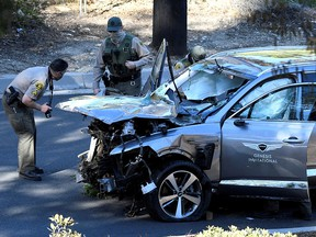 Los Angeles County Sheriff's Deputies inspect the vehicle of golfer Tiger Woods after it was involved in a single-vehicle accident in Los Angeles Feb. 23, 2021.