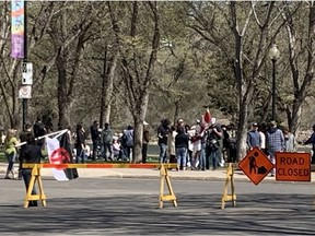 A man carrying a Canadian Nationalist Party flag approaches the crowd gathered for a rally protesting COVID-19 public health orders. (Bryn Levy/Saskatoon StarPhoenix)