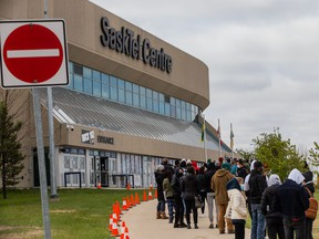 A line of people wait to receive their dose of COVID-19 vaccine at the clinic run by the Saskatoon Tribal Council at Sasktel Centre.