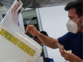 """A man casts his vote at a polling station, in Mexico City, on June 6, 2021. Mexicans began voting Sunday in elections seen as pivotal to President Andres Manuel Lopez Obrador's promised """"transformation"""" of a country shaken by the coronavirus pandemic, a deep recession and drug-related violence."""