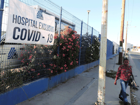 A woman walks by a banner reading 'Hospital exclusive for COVID-19' outside the Cabo San Lucas General hospital as the COVID-19 outbreak continues, in Los Cabos, Mexico, earlier this month.