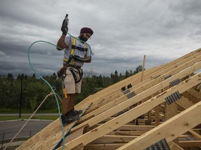 A worker nails plywood on the roof of a home under construction in Edmonton.