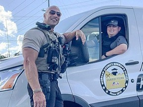 Patrol Lieutenant Eric Fields with the Morgan County Sheriff's Office stands outside police vehicle. Fields bears a striking resemblance to Dwayne 'The Rock' Johnson.