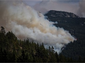 CP-Web. A helicopter carrying a water bucket flies past the Lytton Creek wildfire burning in the mountains near Lytton, B.C., on Sunday, August 15, 2021.