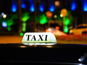 In this stock photo, a glowing taxi sign is seen on the roof of a vehicle at night.