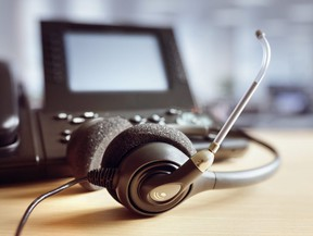 This stock photo shows a call centre headset sitting on an office desk next to a work phone.
