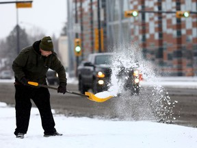 Chris Elliot from Local Lous on 16 Ave. shovels snow as Calgarians woke up to a blast of winter with more snow in the forecast on Thursday November 2, 2017.