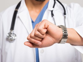 In this stock photo, a doctor wearing a stethoscope checks the time on his wristwatch.