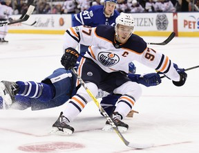 Edmonton Oilers centre Connor McDavid (97) drives to the net past sprawling Toronto Maple Leafs defenceman Ron Hainsey (2) during first period NHL hockey action in Toronto on Sunday, December 10, 2017. THE CANADIAN PRESS/Frank Gunn