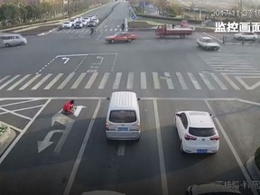 A Chinese man has been fined US$150 after being caught painting over road direction arrows to make his bus commute faster. (YouTube/CGTN)