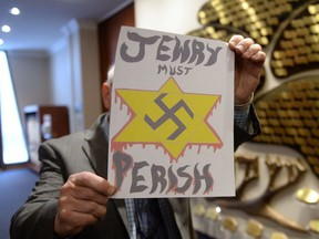 A piece of hate mail is held at a synagogue in Montreal on Tuesday Dec. 19, 2017.