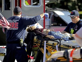 Medical personnel tend to a victim following a shooting at Marjory Stoneman Douglas High School in Parkland, Fla., on Wednesday, Feb. 14, 2018.