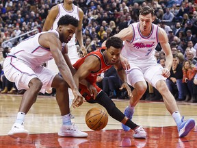 Toronto Raptors Kyle Lowry, centre, battles for the ball with Miami Heat Goran Dragic, right, and Justise Winslow during the first half of NBA basketball action in Toronto, Tuesday February 13, 2018. (THE CANADIAN PRESS/Mark Blinch)