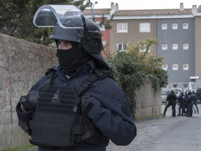 Police cordon off the area of a raid at the residence of a man suspected of killing three people and injuring a dozen others in Carcassonne, southern France, on Friday, March 23, 2018