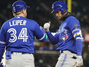 Lourdes Gurriel Jr. of the Toronto Blue Jays is congratulated by first base coach Tim Leiper after he hit an RBI single against the New York Yankees at Yankee Stadium on April 20, 2018