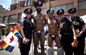 Revellers pose for a photos with police officers at the annual Pride Parade in Toronto on Sunday, July 3, 2016. The group behind Toronto's pride parade wants police to withdraw a bid to take part in the event this year.