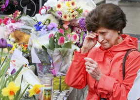 A steady stream of people stop to drop off flowers and read handwritten notes at a memorial wall at Yonge St and Finch Ave. on Wednesday April 25, 2018 after the deadly van attack in North York.