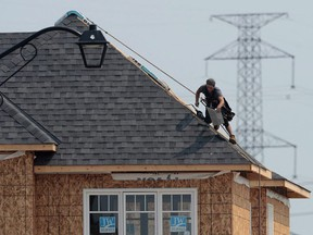 A construction worker shingles the roof of a new home. (THE CANADIAN PRESS)