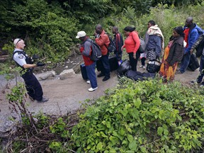 A RCMP officer, left, standing in Saint-Bernard-de-Lacolle, Quebec, advises migrants that they are about to illegally cross from Champlain, N.Y., and will be arrested, on Aug. 7, 2017.