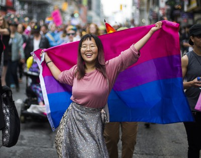 A woman dances with a bisexual pride flag during the Dyke March 2018 along Yonge St. in downtown Toronto, Ont.  on Saturday June 23, 2018. Ernest Doroszuk/Toronto Sun/Postmedia