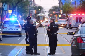 Toronto police investigate a brazen daylight shooting along a busy sidewalk on Queen St. W. near Peter St. that claimed the lives of two men and injured a woman. (Victor Biro photo)