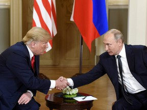 U.S. President Donald Trump, left and Russian President Vladimir Putin shake hands during their meeting in the Presidential Palace in Helsinki, Monday, July 16, 2018.