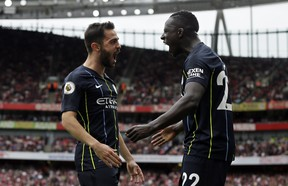 Manchester City's Bernardo Silva (left) celebrates with teammate Benjamin Mendy after scoring his side's second goal on Sunday against Arsenal. (AP PHOTO)