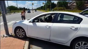 A white sedan hits a pole in an altercation in Brampton captured on video on Friday, Aug. 10, 2018. (Facebook)