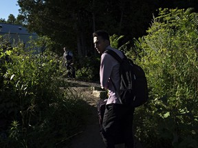 Omer Malik, 19, takes a last look back toward the United States before crossing illegally into Canada at the end of Roxham Road in Champlain, N.Y., on July 18. MUST CREDIT: Photo for The Washington Post by Andre Malerba  N/A
