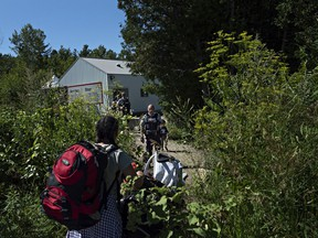 At the end of Roxham Road in Champlain, Fiyori Mesfin, 32, crosses into Canada with her 3-year-old son and 1-year-old daughter, both U.S. citizens. (The Washington Post/Andre Malerba)  N/A