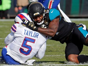 In this Jan. 7, 2018, file photo, Jaguars defensive end Yannick Ngakoue, right, draws a penalty by hitting Bills quarterback Tyrod Taylor (5) with during NFL playoff action, in Jacksonville, Fla.