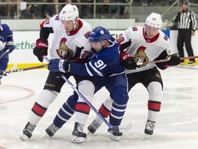 Toronto's John Tavares is checked by Ottawa's Logan Brown and Ryan Dzingel during the second period of the NHL pre-season game between the Maple Leafs and the Senators in Lucan, Ontario, Tuesday, September 18, 2018.