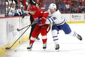 Maple Leafs winger Trevor Moore (right) knocks Red Wings defenceman Joe Hicketts off the puck during pre-season action in Detroit on Saturday.(Paul Sancya/The Associated Press)