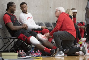 Raptors' Kawhi Leonard (left) gets his knees iced as he speaks to teammate Norman Powell during a team practice in Burnaby, B.C., Tuesday, Sept. 25, 2018. (THE CANADIAN PRESS)