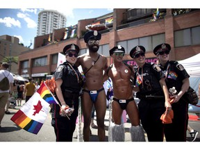 Revellers pose for a photos with police officers at the annual Pride Parade in Toronto on Sunday, July 3, 2016. The organizers of Toronto's Pride Parade say police are once again welcome to participate in the event.