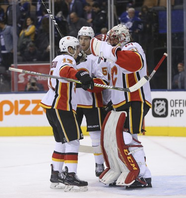 Calgary Flames Johnny Gaudreau LW (13) congratulates teammate Mike Smith G (41) on the 3-1 win  in Toronto on Tuesday October 30, 2018. Jack Boland/Toronto Sun/Postmedia Network
