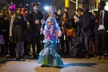 Stella McDiarmid Great, 5, dressed as Ariel, enjoying music played by CIUT 89.5 FM from their booth as Halloween comes to the Village as a part of Church St. is closed to traffic for Halloween on Church in Toronto, Ont. on Wednesday October 31, 2018. Ernest Doroszuk/Toronto Sun/Postmedia