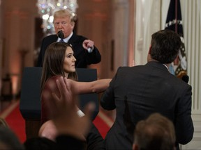 U.S. President Donald Trump looks on as a White House aide tries to take away a microphone from CNN reporter Jim Acosta during a news conference at the White House in Washington, Wednesday, Nov. 7, 2018.