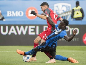 Montreal Impact defender Bacary Sagna Sagna, right, challenges Toronto FC's Jonathan Osorio during second half MLS soccer action in Montreal, Sunday, Oct. 21, 2018. (THE CANADIAN PRESS/Graham Hughes)