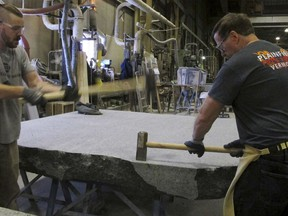 In this Tuesday, Jan. 8, 2019 photo, stone cutters Evan Ladd, left, and Andy Hebert cut a piece of granite at Rock of Ages in Barre, Vt. The granite will be formed into stone monoliths that will be part of a permanent dedication to ground zero rescue and recovery workers expected to be unveiled in late May at the National September 11 Memorial & Museum in New York.