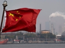 This picture taken on March 22, 2018 shows a Chinese flag fluttering in front of the Shanghai Gaoqiao Company Refinery in Shanghai.