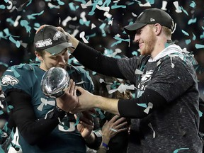 In this Feb. 4, 2018, file photo, Philadelphia Eagles quarterback Carson Wentz, right, hands the Vincent Lombardi trophy to Nick Foles after the Eagles defeated the New England Patriots 41-33 in the NFL Super Bowl 52 football game in Minneapolis. (AP Photo/Frank Franklin II, File)
