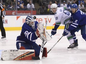 Maple Leafs goaltender Michael Hutchinson (30) makes a save as Maple Leafs defenceman Ron Hainsey (2) and Vancouver Canucks centre Bo Horvat (53) look on during second period in Toronto on Saturday. THE CANADIAN PRESS/Nathan Denette