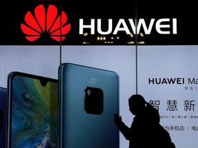 In this Dec. 11, 2018, file photo, a woman browses her smartphone as she walks by a Huawei store at a shopping mall in Beijing.