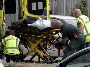 "Ambulance staff take a man from outside a mosque in central Christchurch, New Zealand, Friday, March 15, 2019.  Multiple people were killed in mass shootings at two mosques full of worshippers attending Friday prayers on what the prime minister called ""one of New Zealand's darkest days,"" as authorities detained four people and defused explosive devices in what appeared to be a carefully planned attack. (AP Photo/Mark Baker) ORG XMIT: XMB102"